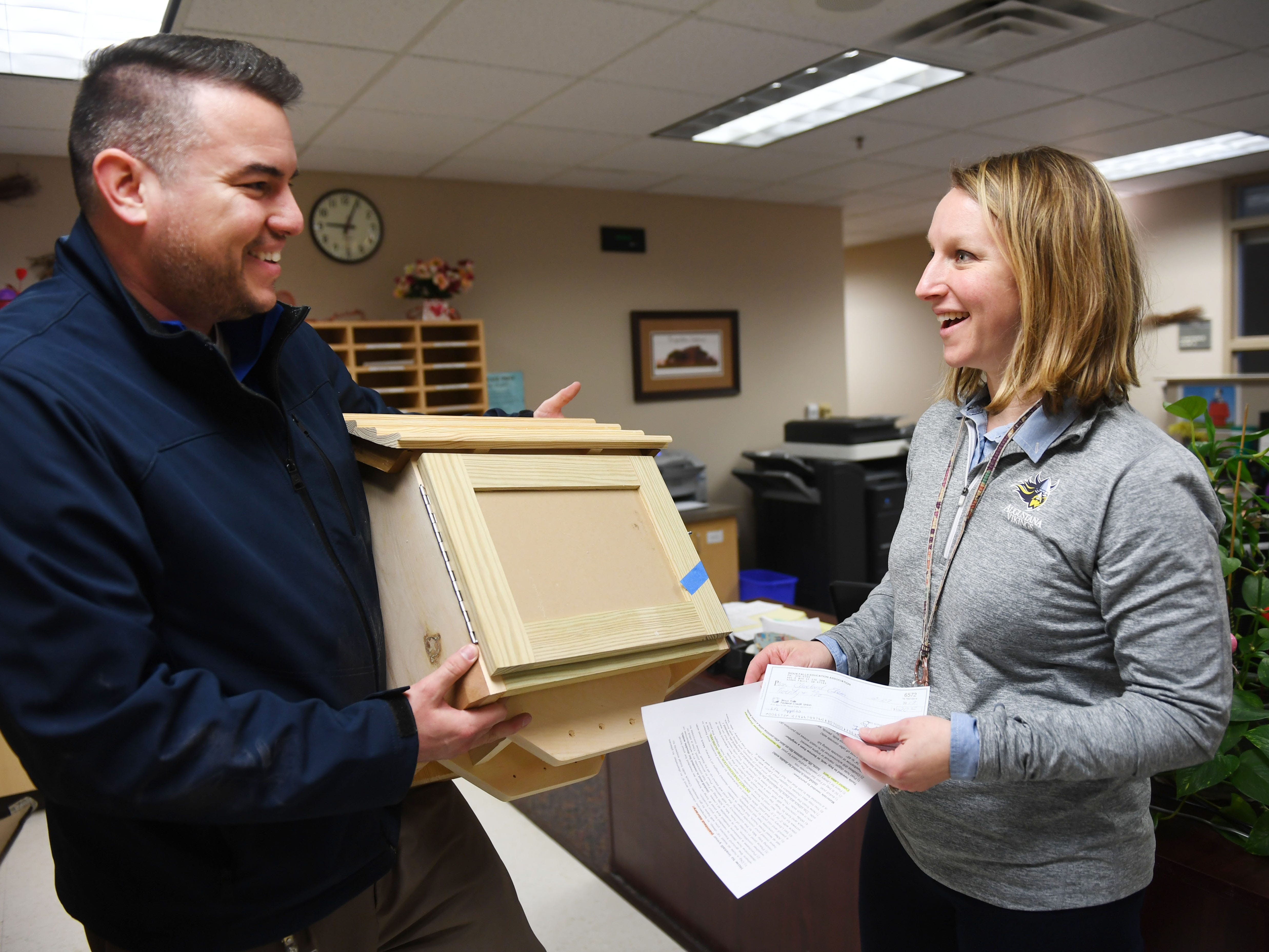 Tony Martinet, Sioux Falls Education Association President, delivers a Little Free Library to Cleveland Elementary School's assistant principal Amanda Bosch Friday, March 1, in Sioux Falls. Martinet went to six elementary schools to drop of the Little Free Libraries. He said they have a total of 10 Little Free Libraries they want to give to schools. Four of the libraries are still available.