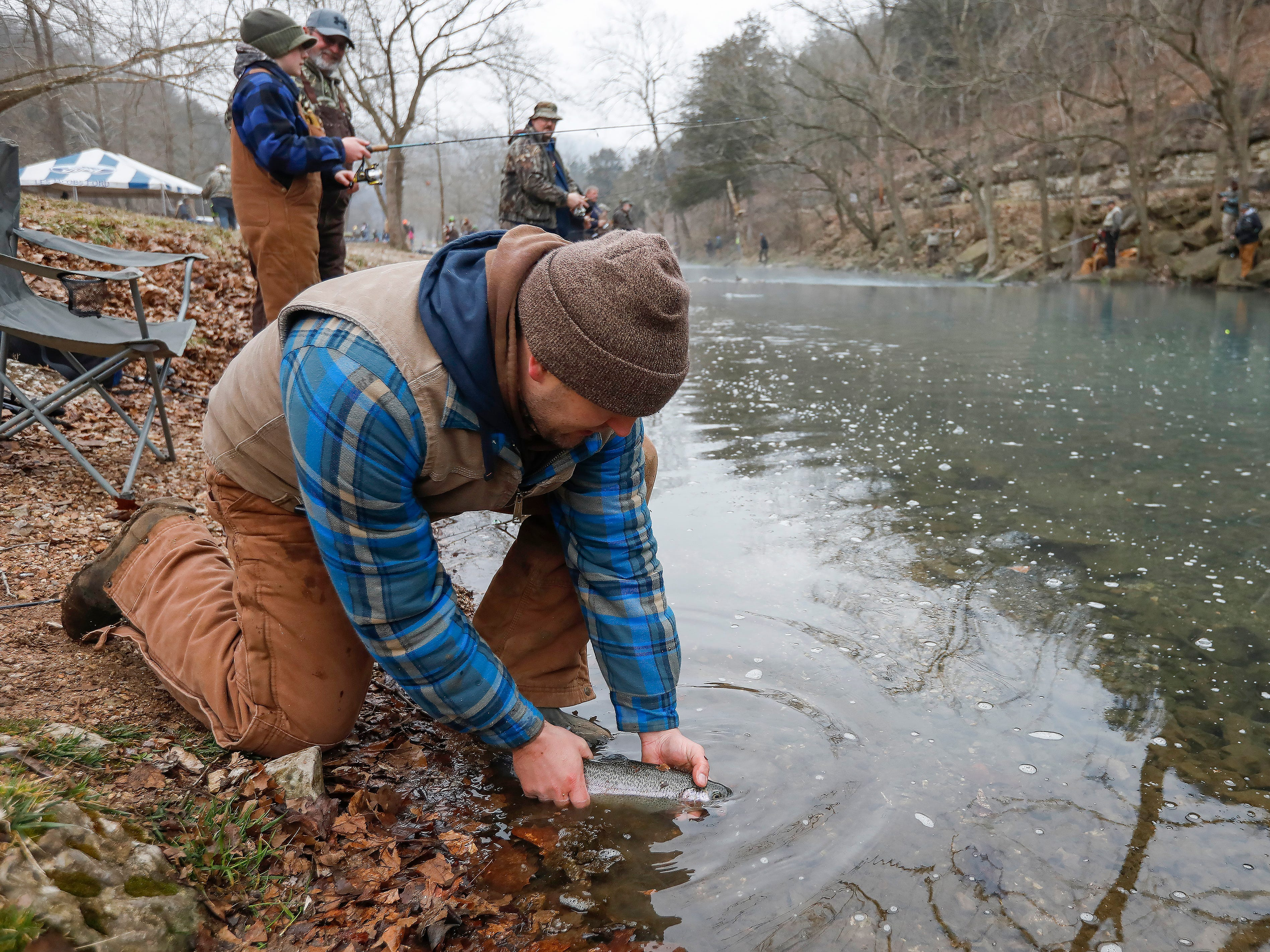 Zach Bellah, of Marrionville, releases a trout he just caught on opening day of trout season at Roaring River State Park on Friday, Mar. 1, 2019.