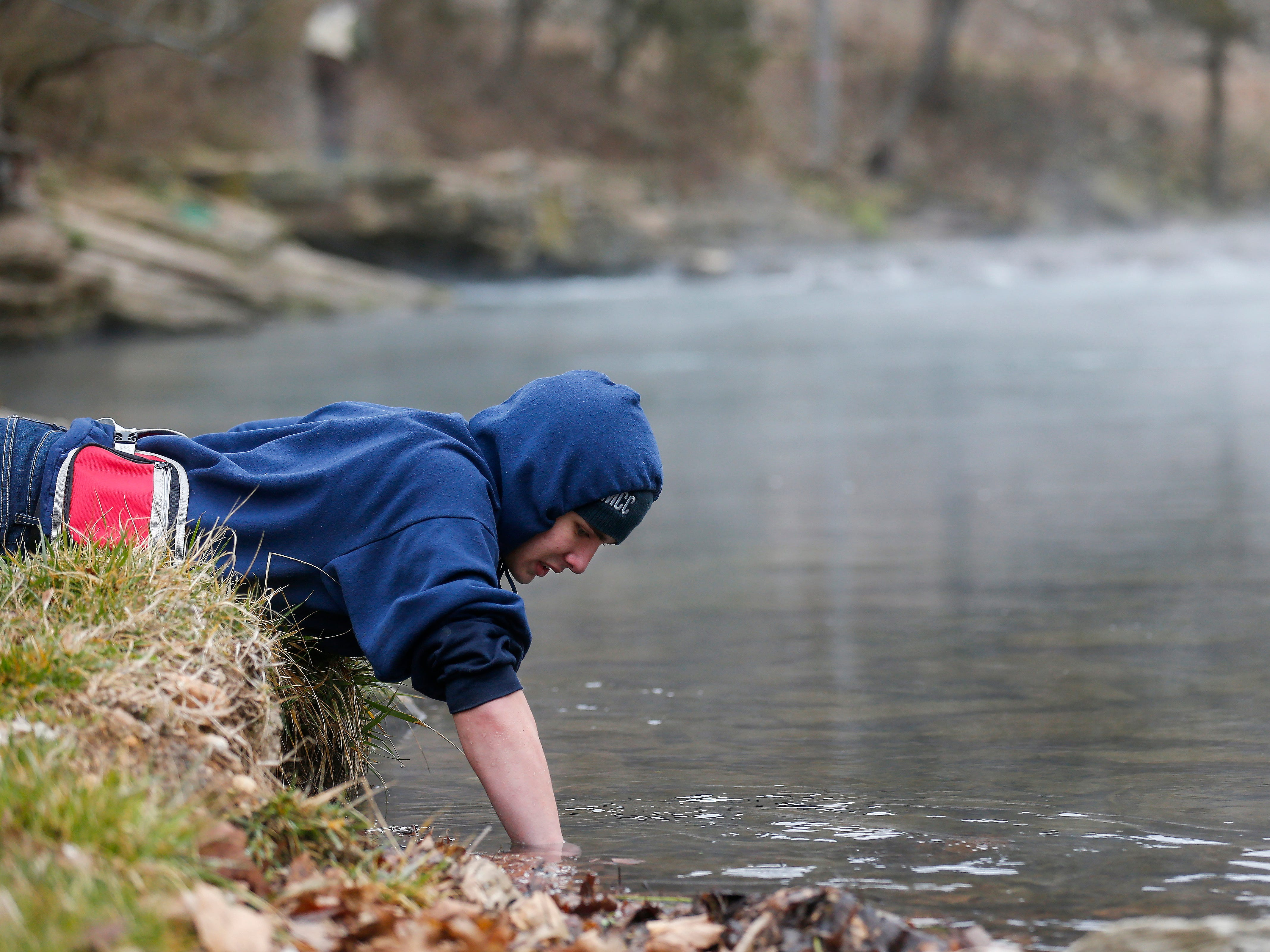 Riley Jones, of Pea Ridge, Arkansas, tries to grab a crawfish with his bare hand during opening day of trout season at Roaring River State Park on Friday, Mar. 1, 2019.
