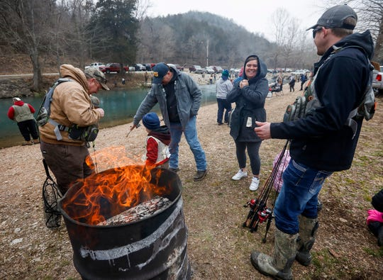 People gather around a fire to warm up on opening day of trout season at Roaring River State Park on Friday, Mar. 1, 2019.
