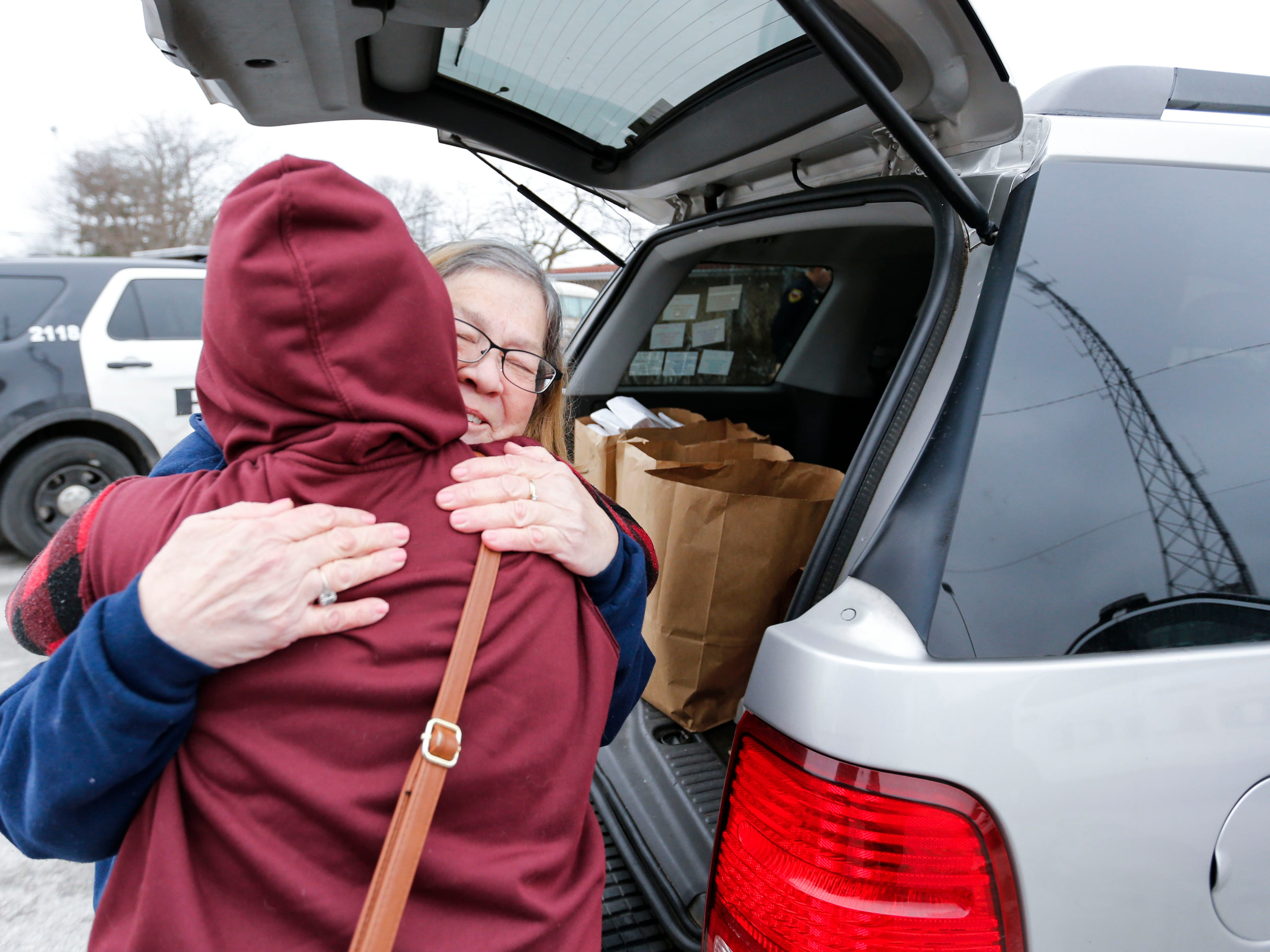 Marti Knaur recieved a hug from a homeless woman as she hands out sack lunches outside the Veterans Coming Home Center on Friday, March 1, 2019.