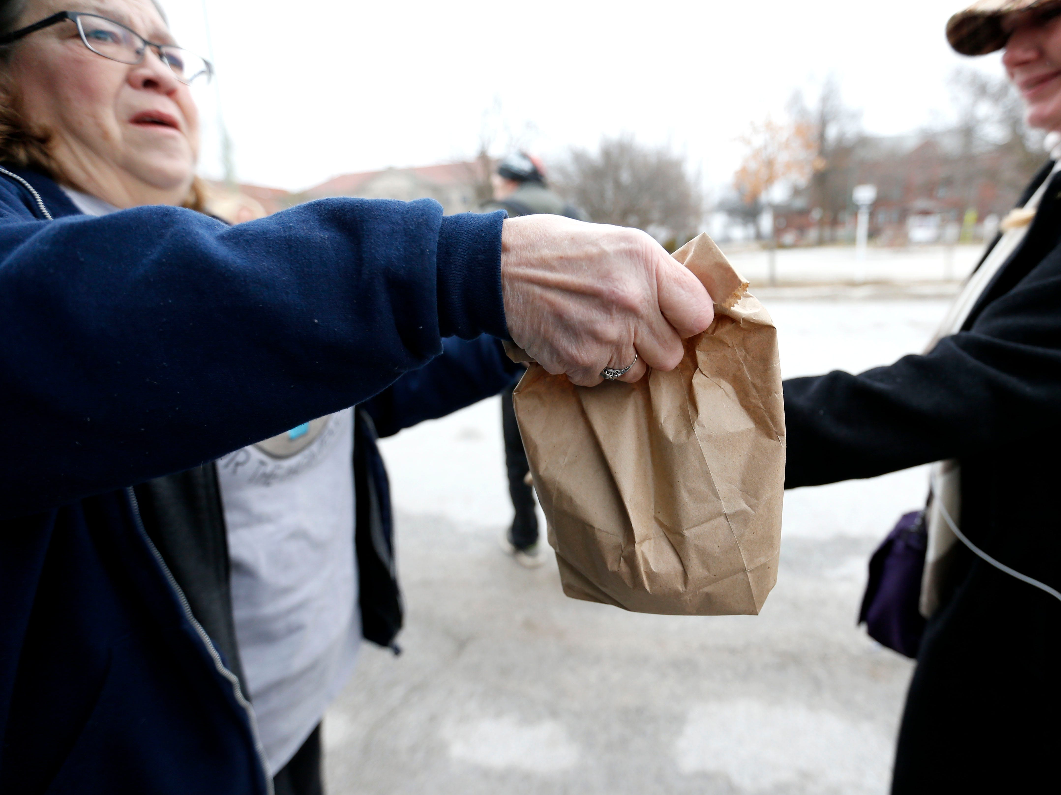 Marti Knaur hands out sack lunches to homeless people outside the Veterans Coming Home Center on Friday, March 1, 2019.