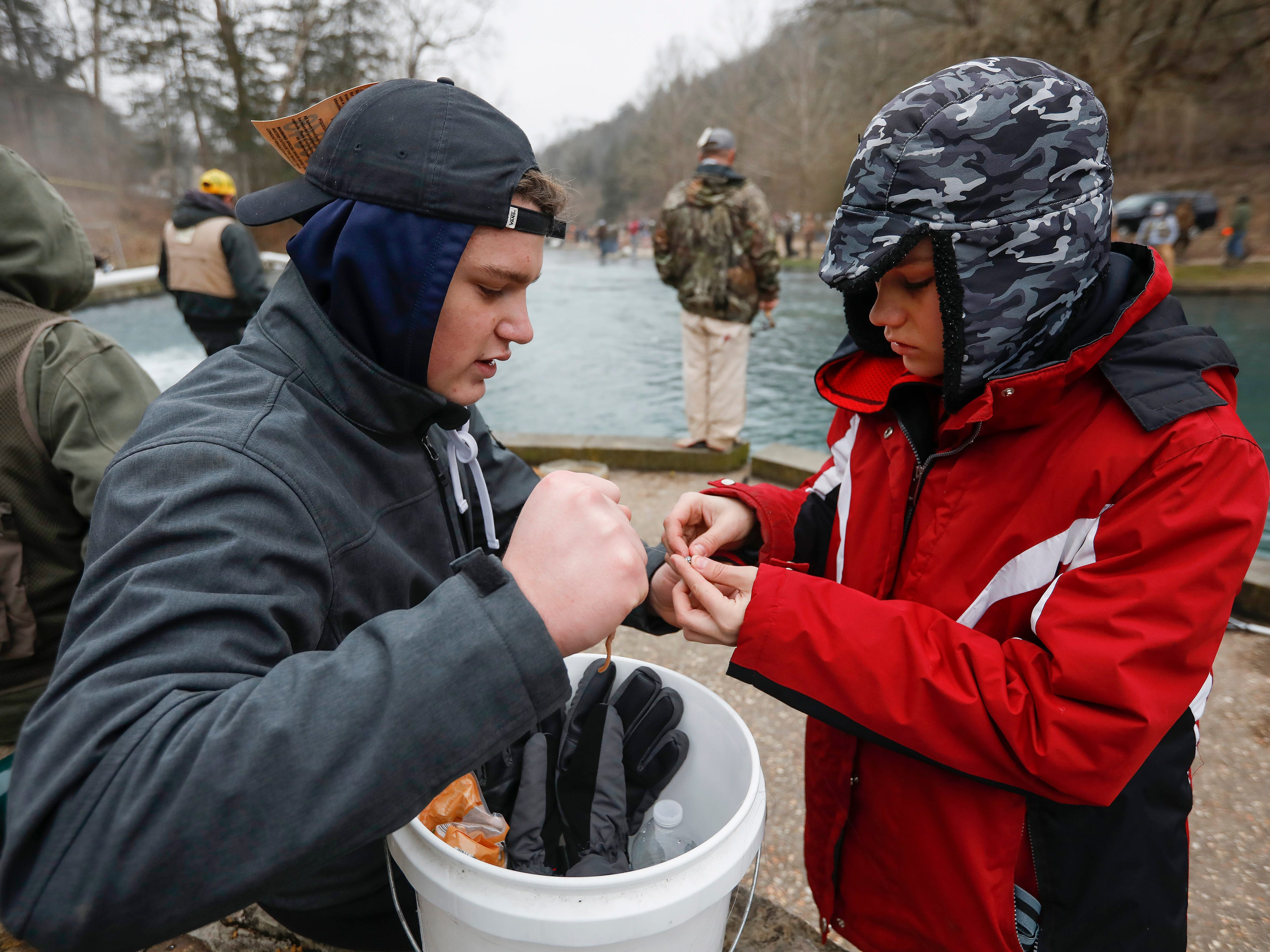 Kyler Miles, 17, left, and Tuff Schureman, 12, both of Rogers, Arkansas, attach a weight to a fishing line during opening day of trout season at Roaring River State Park on Friday, Mar. 1, 2019.