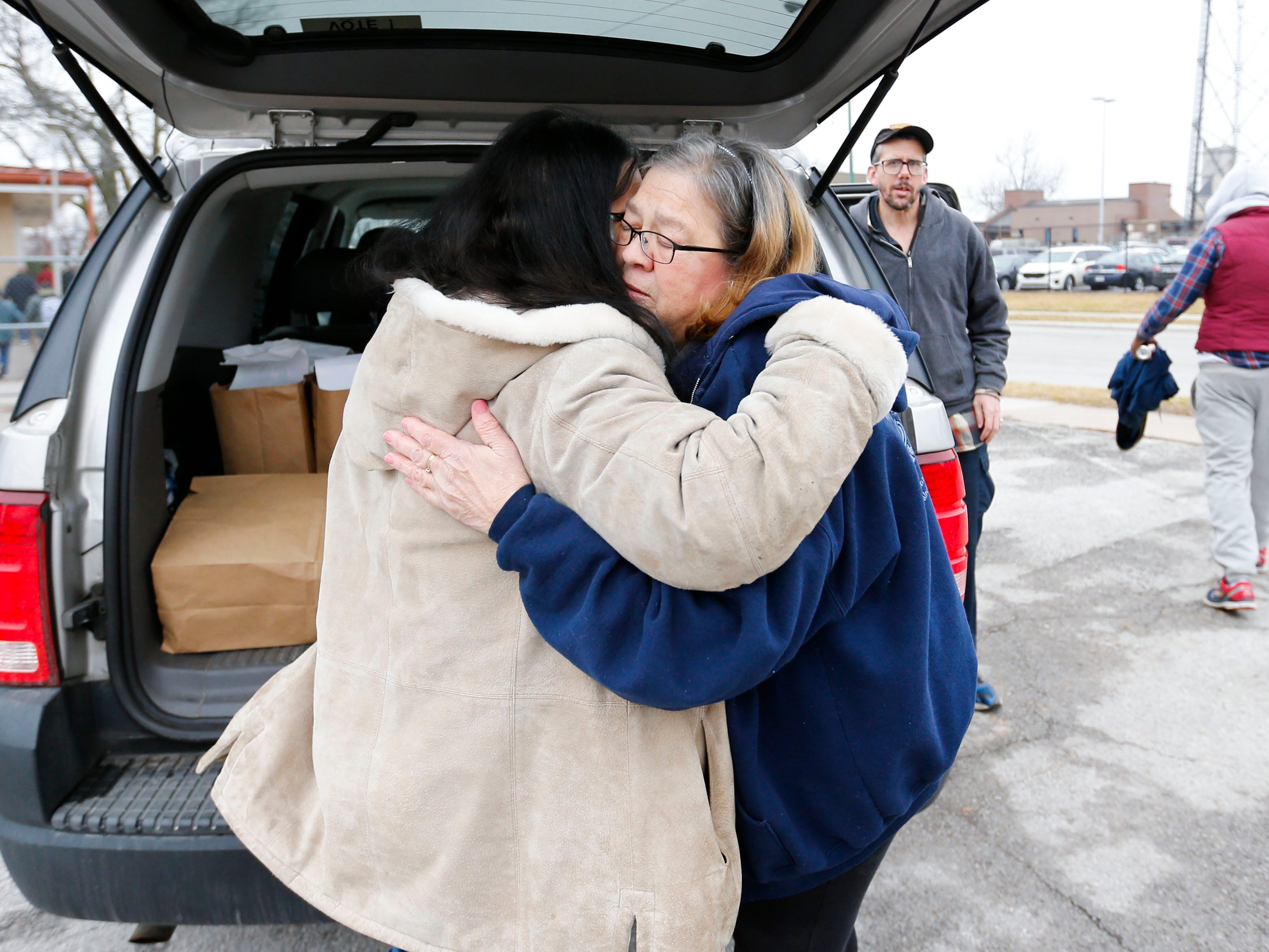 Marti Knaur receives a hug from a homeless woman as she hands out sack lunches outside the Veterans Coming Home Center on Friday, March 1, 2019.
