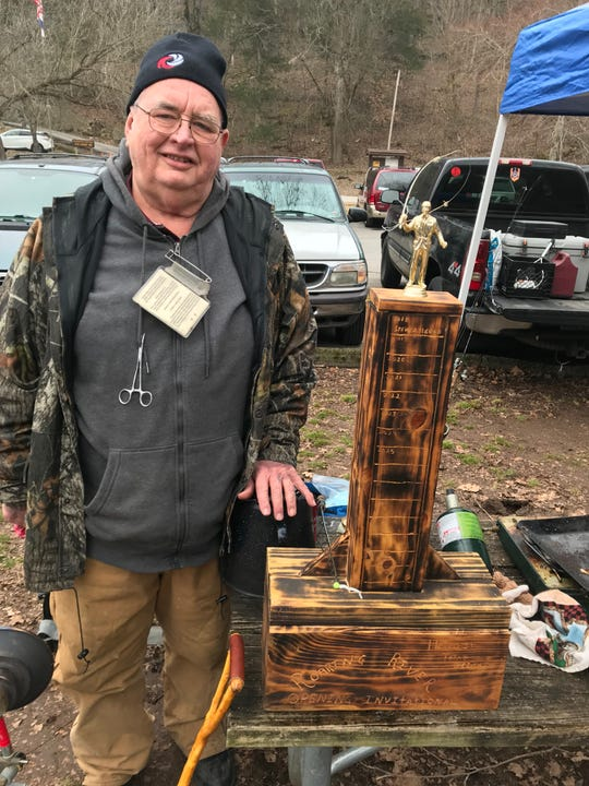 Joplin trout angler Tom Allgood shows off the handmade traveling trophy that's awarded to the family member who brings in the heaviest stringer of fish.