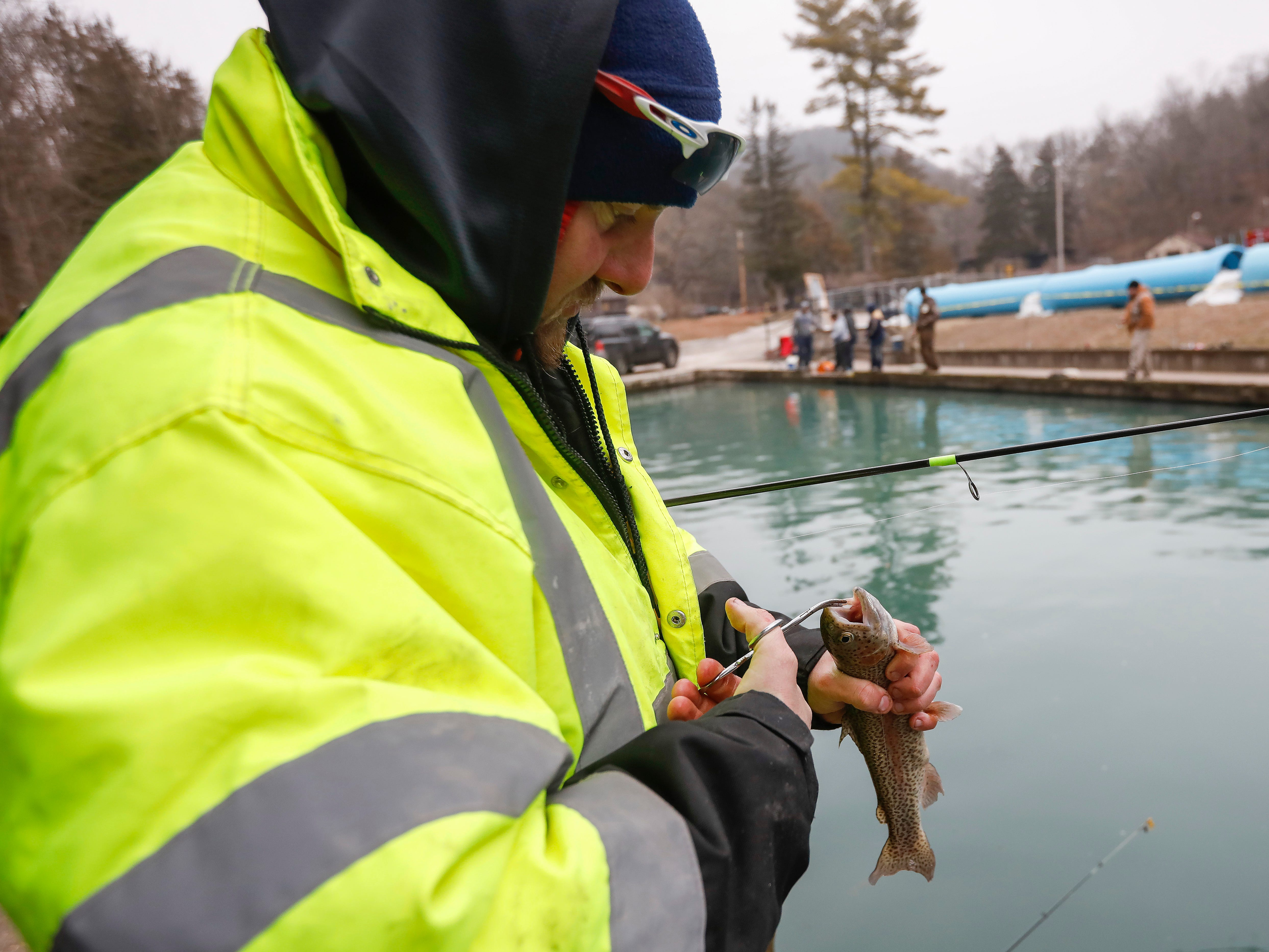 Stephen Davis unhooks the trout he caught during opening day of trout season at Roaring River State Park on Friday, Mar. 1, 2019.