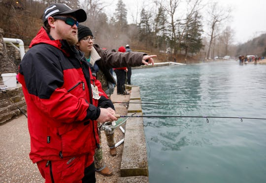 Candace Gaze points out a good spot to cast for Joshua Wishon on opening day of trout season at Roaring River State Park on Friday, Mar. 1, 2019.