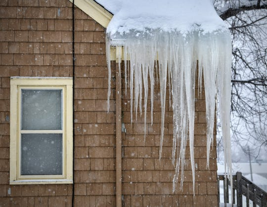Large icicles and an ice dam form on the roofline of a home as more snow continues to fall Friday, March 1, in St. Cloud.