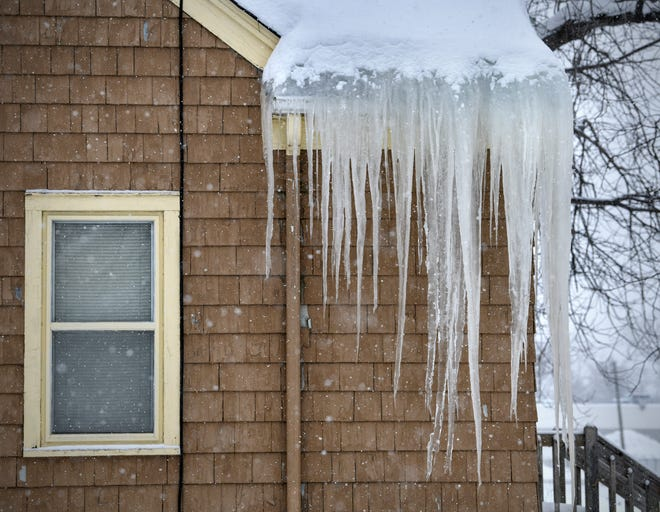 Large icicles and an ice dam form on the roofline of a home as more snow continues to fall Friday, March 1, 2019, in St. Cloud.