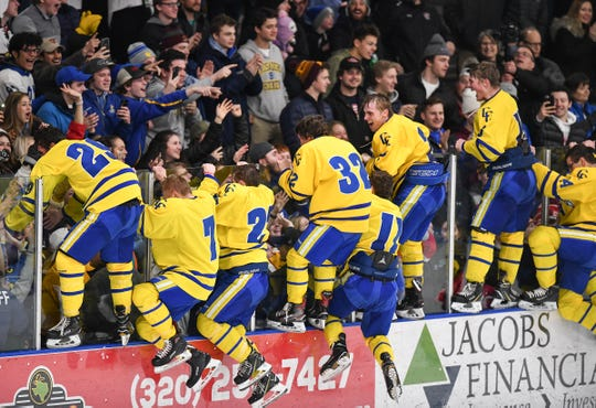 Cathedral players jump to celebrate with their fans in the student section after their 4-1 win in the Section 6A championship game Thursday, Feb. 28, at the MAC in St. Cloud.