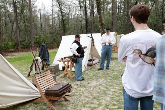 A man demonstrates how to use a rifle at the 42nd Annual Battle of Natural Bridge Reenactment, Friday March 1, 2019.