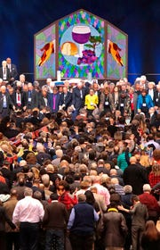 Delegates gather and hold hands on the arena floor during a prayer before a major vote for the One Church Plan at the special session of the United Methodist Church General Conference at the America's Center in downtown St. Louis on Tuesday, Feb. 26, 2019. (Cristina M. Fletes/St. Louis Post-Dispatch via AP)