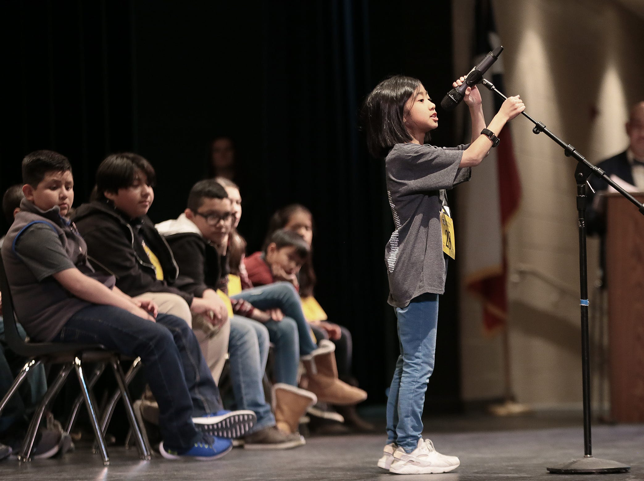Lucienne Saranghilo reaches for the microphone as she prepares to spell at the 2019 El Paso Regional Spelling Bee Friday at Bowie High School.