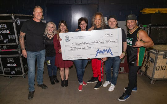 El Pasoans Fighting Hunger received a check for $10,000 generated from the Metallica concert Thursday night. From left are Metallica lead singer James Hetfield; Stefania Garza, volunteer coordinator; Bailey Eiland, fund development manager for the organization; Terri Wyatt, chief development officer; guitarist Kirk Hammett; drummer Lars Ulrich; and bassist Robert Trujillo.  organization ..