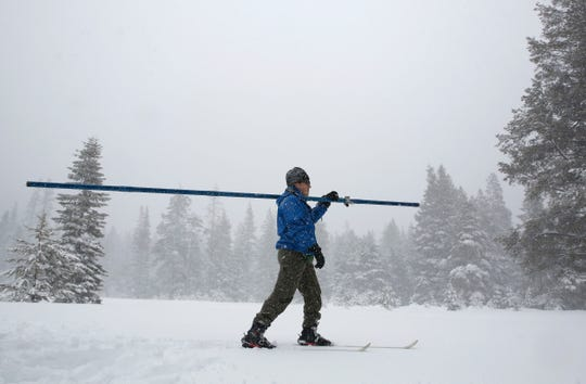 Snow falls as John King of the Department of Water Resources, crosses a meadow while conducting the third manual snow survey of the season at the Phillips Station near Echo Summit on Thursday. The survey found the snowpack at 113 inches deep with a snow water equivalent of 43.5 inches at this location at this time of year.