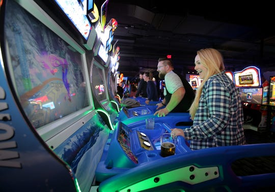 Michelle Criger, right, and Justin Todd try their skills on the video game Snow Boarder at the new Thousand Oaks Dave & Buster's.