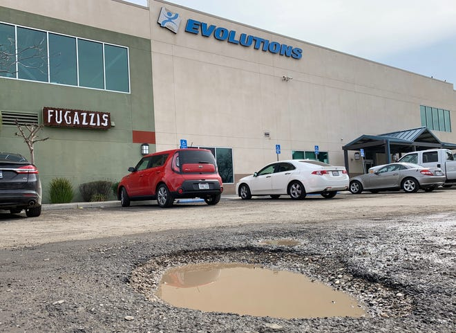 Potholes line the asphalt outside of Evolution's Fitness & Wellness Center in Tulare on Friday, March 1, 2019.