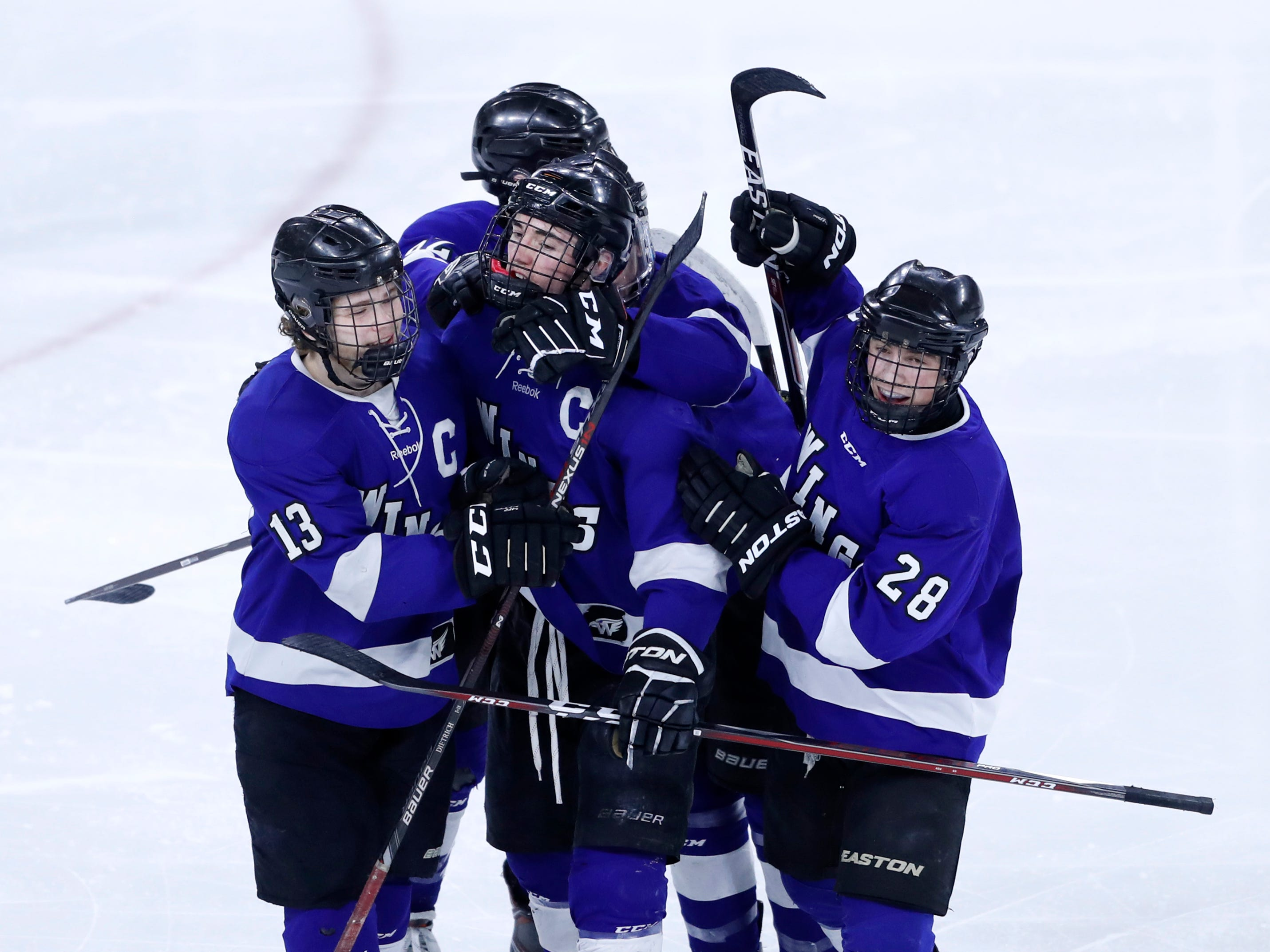 Teammates gather around Waukesha North Co-op's Chad Larsen after he scored a goal against Wausau West during the WIAA State Hockey Tournament quarterfinals Thursday, Feb. 28, 2019, at Veterans Memorial Coliseum in Madison, Wis.