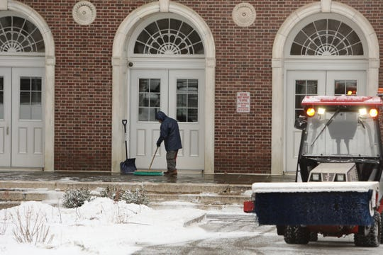A worker clears snow in front of Washington Irving School in Tarrytown on Friday, March 1, 2019.