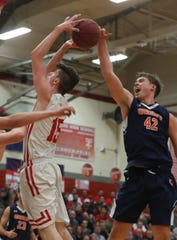 Nicholas Townsend of Horace Greeley  blocks a shot by Charlie Garrison of Tappan Zee during the Class A semifinal basketball game at Tappan Zee High School Feb. 28, 2019. Tappan Zee defeated Greeley 67-60 in double overtime.