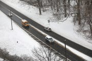A school bus drives along wet pavement in Yonkers as snow covers the ground on Friday, March 1, 2019.