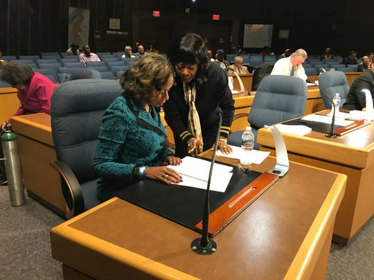 Zanthia Oliver hands a city council agenda to new 1st District councilwoman Linda Gray