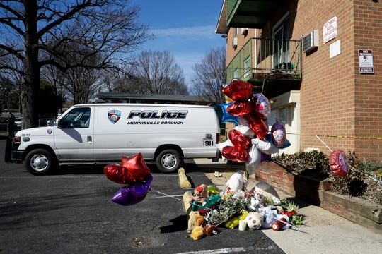 "A makeshift memorial is seen outside the Robert Morris Apartments, Thursday, Feb. 28, 2019, in Morrisville, Pa. A mother and her adult daughter killed five of their close relatives, including three children, and were found ""disoriented"" after child welfare authorities arrived for a surprise visit to their trashed apartment outside Philadelphia, police and prosecutors said Tuesday. (AP Photo/Matt Slocum)"
