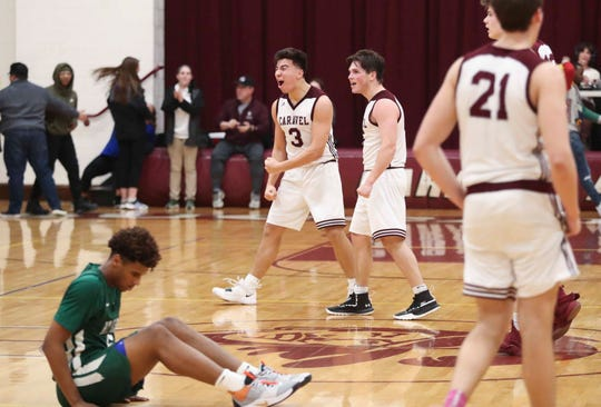 Caravel's Brandon Sengphachanh (3) and Kevin Keister celebrate as Mount Pleasant's Yshaad Butcher has an opposite reaction to Caravel's 53-50 win in the second round of the DIAA state high school tournament Thursday.