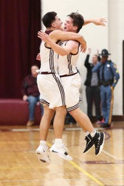 Caravel's Brandon Sengphachanh (left) and Kevin Keister celebrate in the final moments of Caravel's 53-50 win in the second round of the DIAA state high school tournament Thursday.