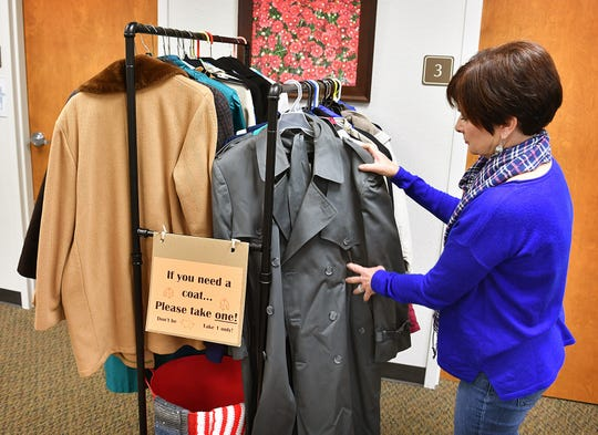 Kris Gossom, executive director of Interfaith Outreach Services, hangs up some of the newest coats acquired for their community coat closet. Clients are encouraged to take a coat if they need one.