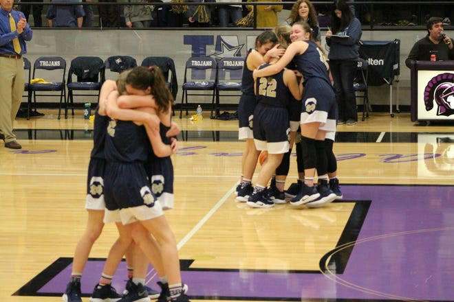 The Notre Dame Lady Knights embrace each other after defeating Lubbock Kingdom on Friday and punching their ticket to the TAPPS A state title game.