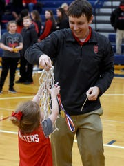 Sheridan coach J.D. Walters hands the net to his daughter following a 51-38 win against Circleville in a Division II district final. Walters has an 89-13 record in four years, and he has also coached boys cross country to a state runner-up finish.