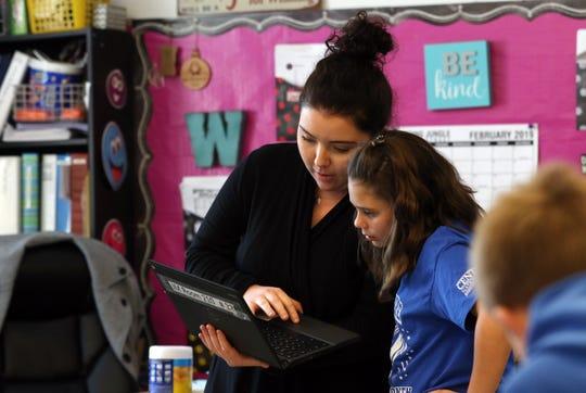 Substitute teacher Lauren Williams talks with Alyssa Gimenez during a fourth grade class at Zanesville's John McIntire Elementary School on Friday.