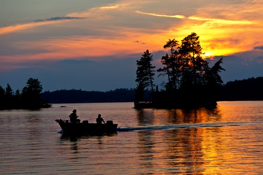 Fisherman fishing on a small boat at sunset over Burntside Lake, Ely Minnesota. Located in the Superior National Forest. Burntside Lake a popular tourist destination in the summer in Minnesota. Beautiful scenic area adjacent to the Boundary Waters Canoe Area.
