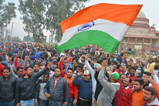 An Indian waves national flag as others shout slogans while they wait to welcome Indian pilot at India Pakistan border at Wagah, 28 kilometers (17.5 miles) from Amritsar, India, Friday, March 1, 2019.