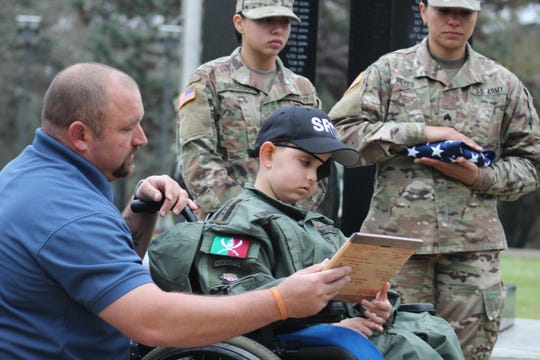 Drake Quibodeaux (right), 8, looks at a plaque given to him by members of the 519th Military Police Battalion as his father, Christopher Quibodeaux, holds it.