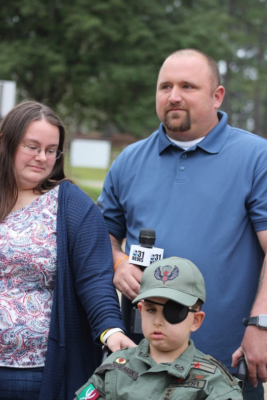 Parents Danielle and Christopher Quibodeaux stand behind their son, 8-year-old Drake Quibodeaux, at Fort Polk on Friday.