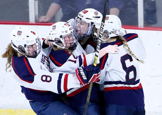 Tori Nelson (8), Annika Horman (12), and Lauryn Hull (6) rush into Maddy Jablonski (10) after she scored the game-winning goal against Hudson in double overtime to lead the Fox Cities Stars to the WIAA state hockey championship Saturday in Madison.