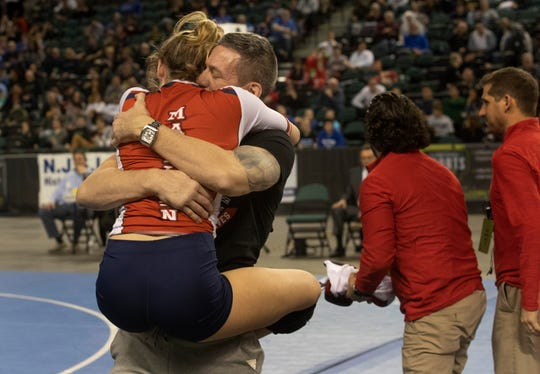 Jesse Johnson jumps into the arms of her dad Bobby Johnson after winning her state champions. Jesse Johnson, Manalapan pinned Veronica Whitacre, Monroe in 136 lbs final. NJSIAA State Girls Wrestling finals on Saturday,  March 2, 2019 in Atlantic City.