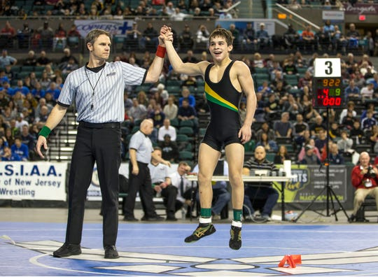 Brick Memorial's Vincent Santaniello gets his hand raised after he finished third in the state at 113 pounds on Saturday.