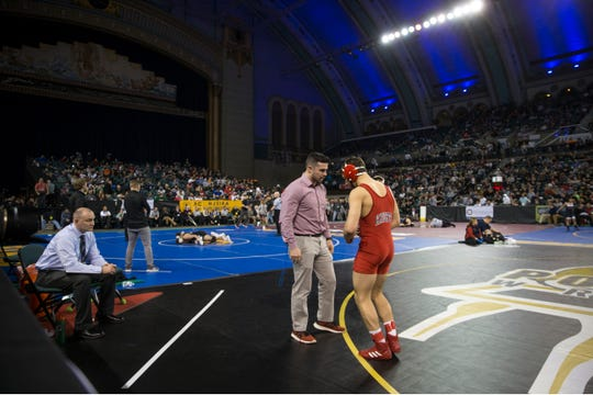Wall senior 160-pounder Robert Kanniard talks with assistant coach Drew Reca while Crimson Knights' head coach Brian Fischer sits in the chair before his semifinal match with Manalapan's Matt Benedetti.