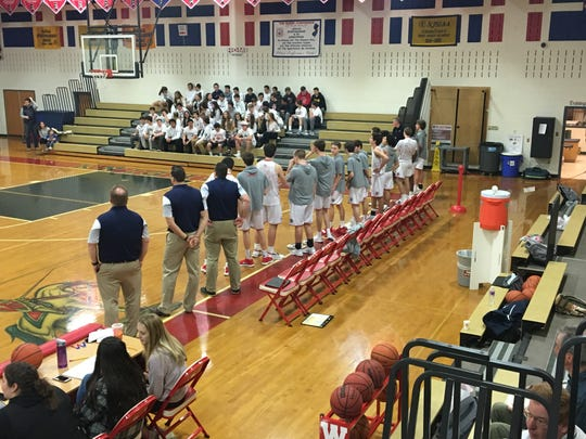 The Wall boys basketball team observes the national anthem before the game against Ewing