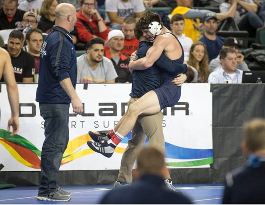 Howell junior 170-pounder Shane Reitsma jumps into the arms of Rebels' assistant coach Pete Reilly after he defeated Delbarton's A.J. Lonski in the 170-pound semifinal Friday night.