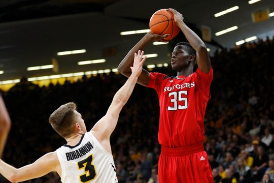 Rutgers forward Issa Thiam (35) shoots a 3-point basket over Iowa guard Jordan Bohannon during the first half