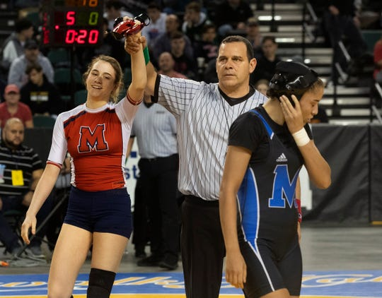 Jesse Johnson has her hand raised as Monroe's Veronica Whitacre walks off disapointed.  Jesse Johnson, Manalapan pinned Veronica Whitacre, Monroe in 136 lbs final. NJSIAA State Girls Wrestling finals on Saturday,  March 2, 2019 in Atlantic City.