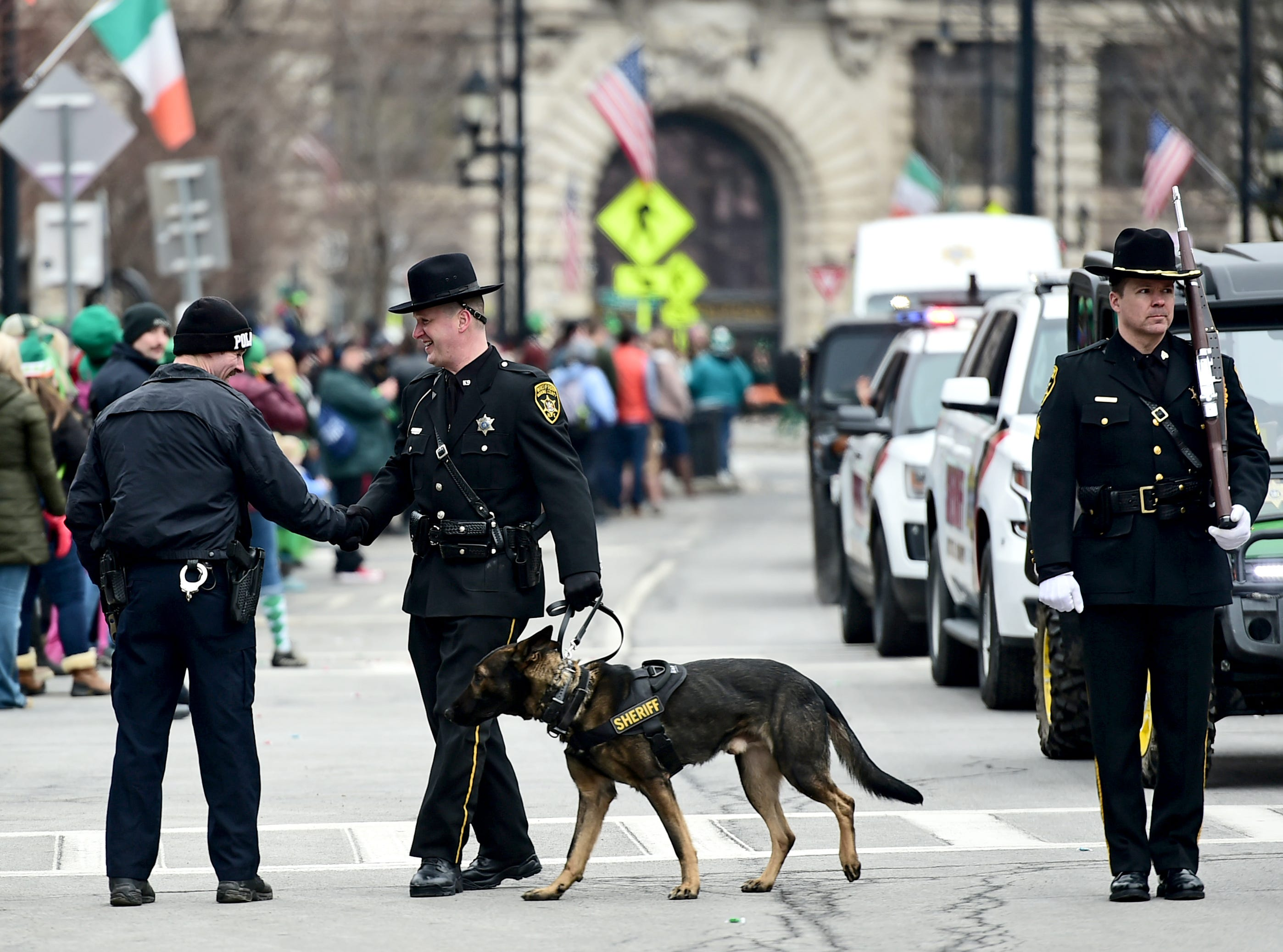 A member of the Broome County Sheriff's Department shakes hands with a Binghamton Police Officer along the parade rout during the annual St. Patrick's Day Parade in downtown Binghamton. March 2, 2019.