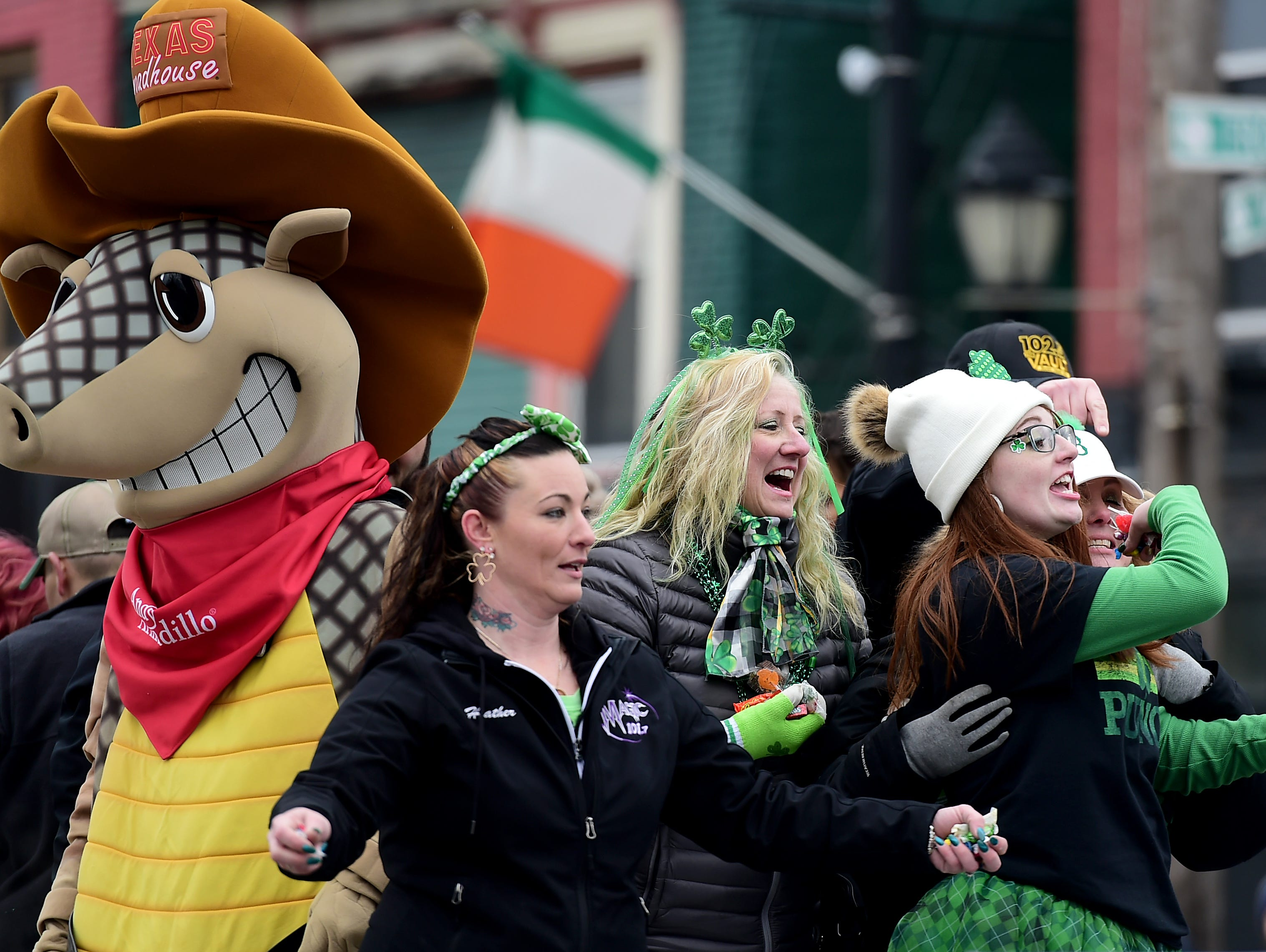 The employees of Texas Roadhouse throw candy from their float during the annual St. Patrick's Day Parade in downtown Binghamton. March 2, 2019.