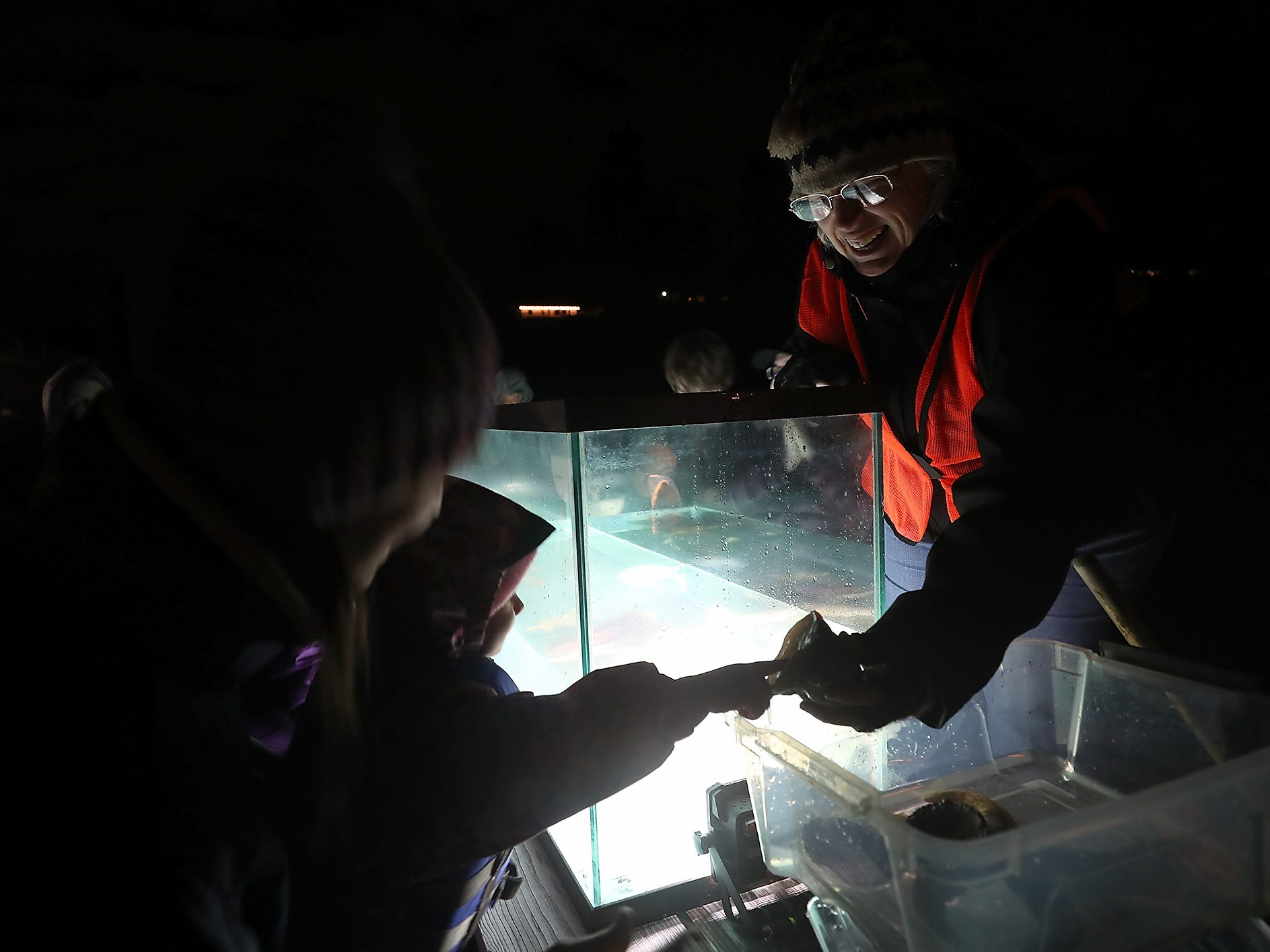 Kitsap Beach Naturalist Victoria Poage smiles as Caroline Stottlemyer, 2, touches a sea snail during the Night Time Pier Peer at the Brownsville Marina on Friday, March 1, 2019.