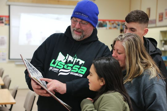 "Visitors to Central Kitsap Middle School enjoy an old annual at ""Central Kitsap Middle School Through the Decades"" on Tuesday. The school, built in 1959, will be demolished this spring. Students will move to a new middle school building after spring break."