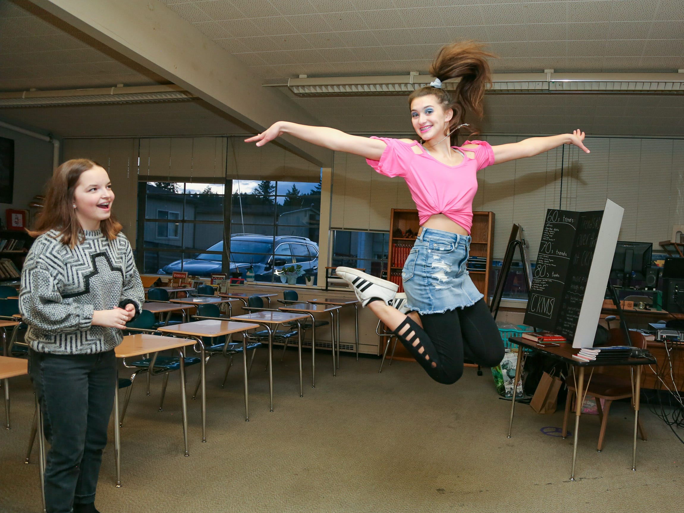 "Central Kitsap Middle School student Tegan Arthur shows off her 1980s-inspired outfit  as student Sarah Witham watches at ""Central Kitsap Middle School Through the Decades"" on Feb. 26, 2019. The school, built in 1959, will be demolished this spring. Students will move to a new middle school building this spring."